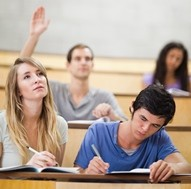 Portrait of students taking notes while their classmate is raising his hand